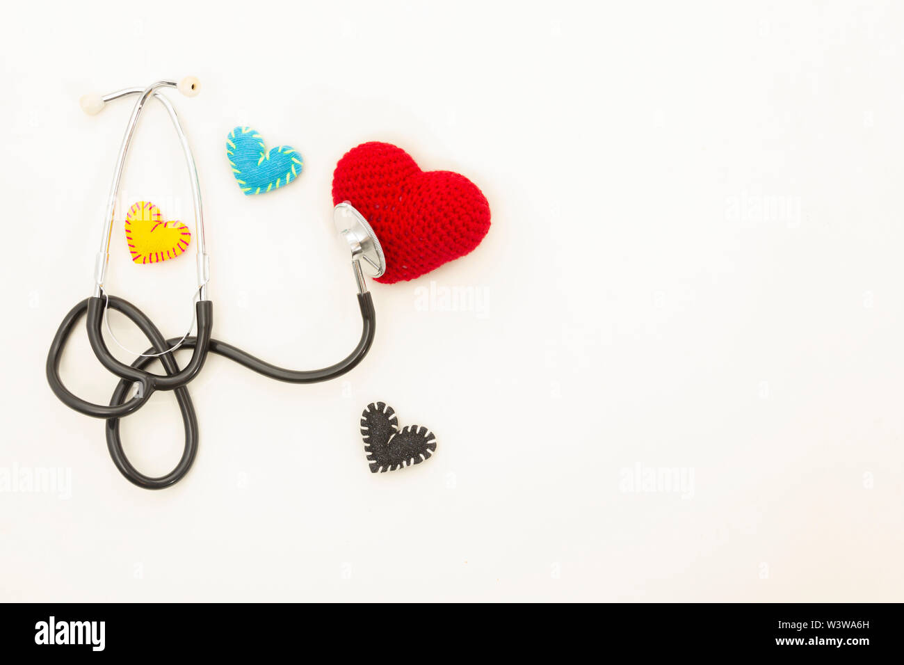 Heart health and prevention concept. Stethoscope and red heart of crochet on white isolated background with space for text. Stock Photo