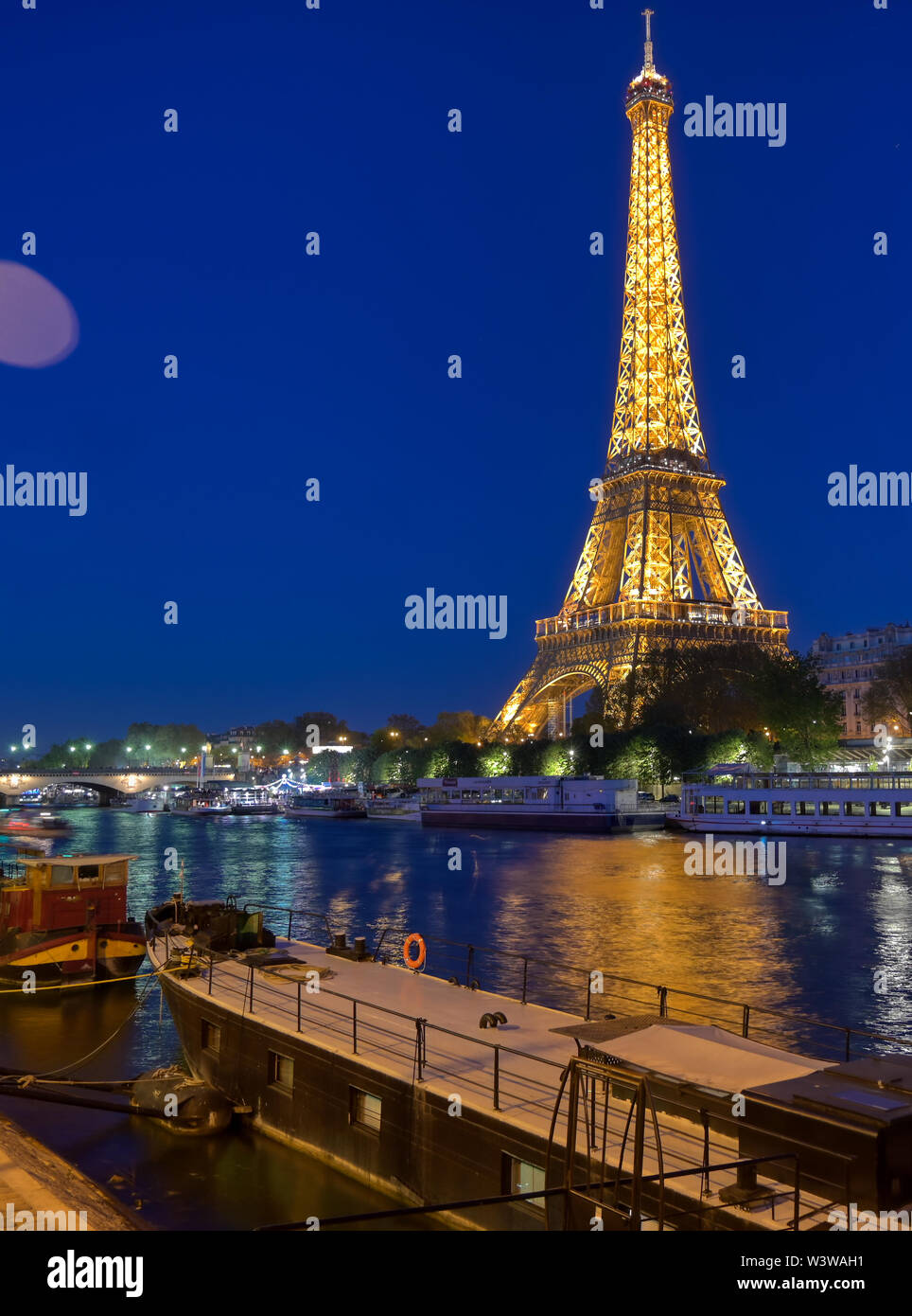 Paris, France - April 20, 2019 - A view of the Eiffel Tower at night across the River Seine in Paris, France. - Stock Image