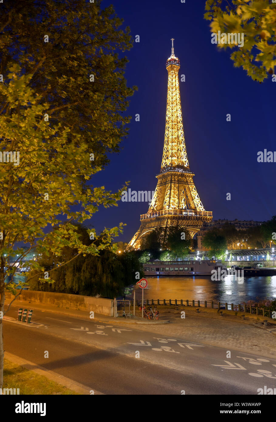 Paris, France - April 20, 2019 - A view of the Eiffel Tower at night across the River Seine in Paris, France. Stock Photo