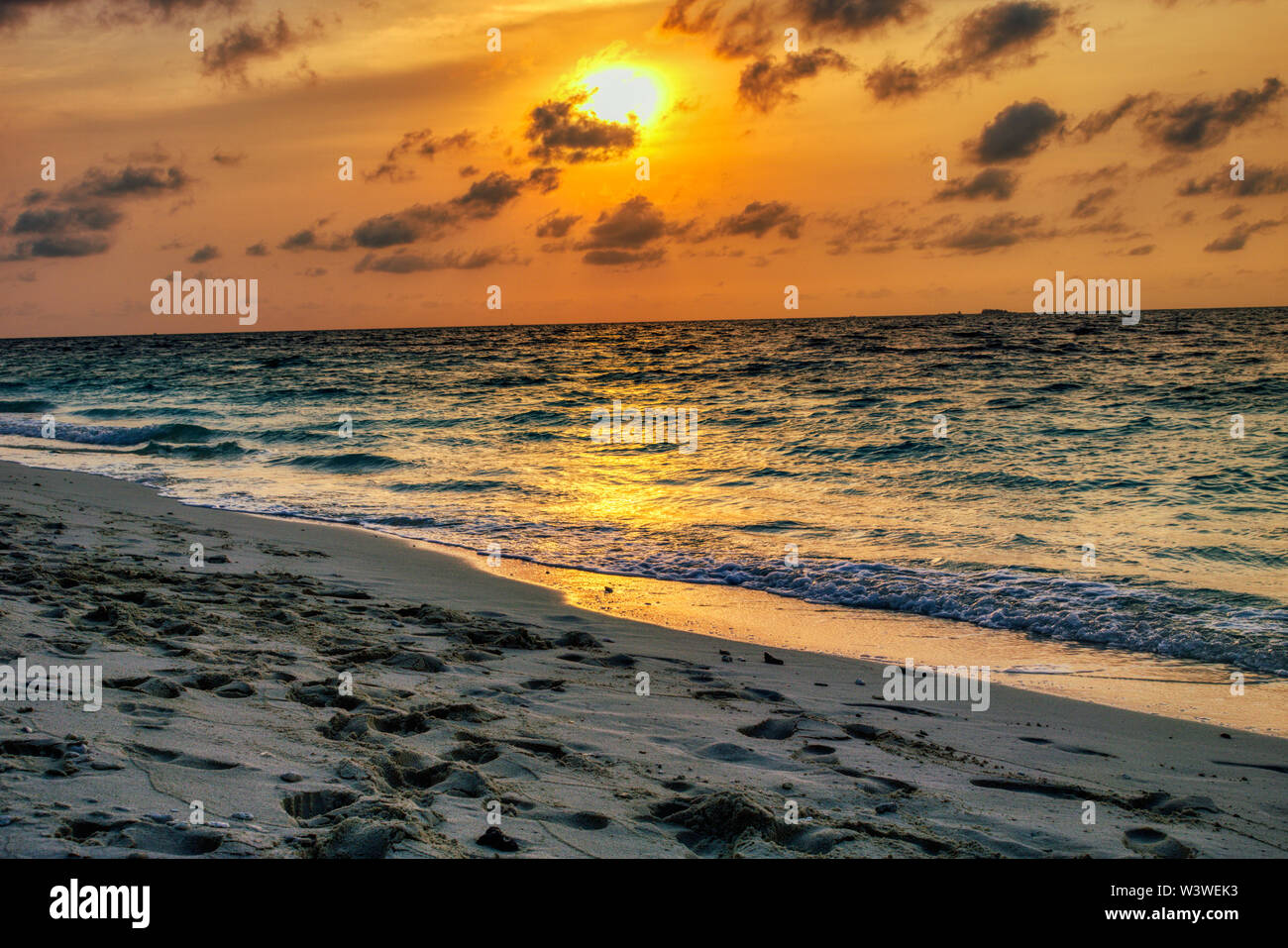 This unique picture shows the gigantic sunset in the Maldives. you can easily see how the sky bursts and everything turns orange - Stock Image