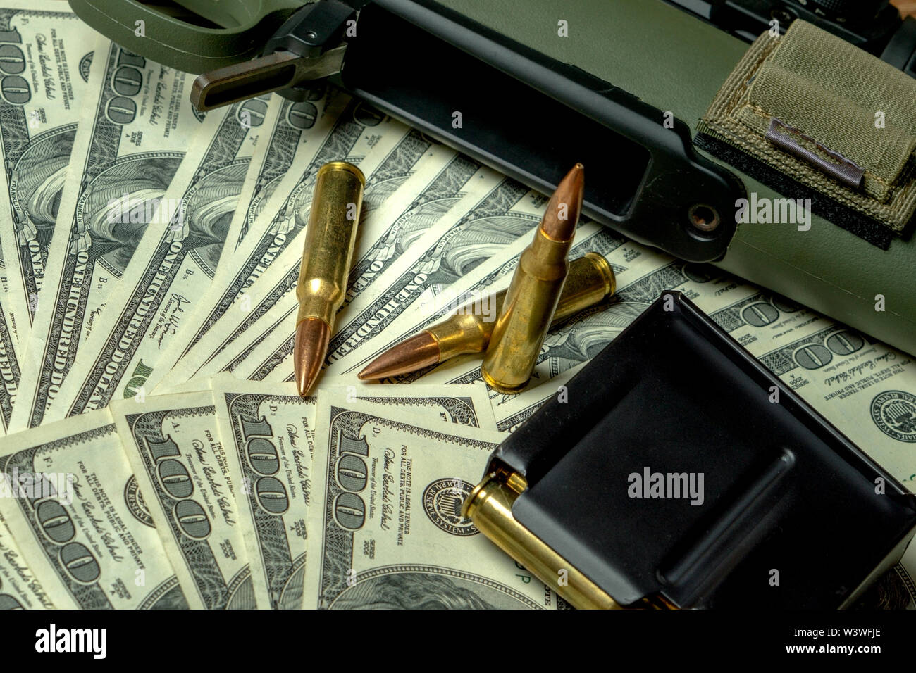 Rifle, magazine and cartridges on hundred dollar bills. Concept for crime, contract killing, paid assassin, terrorism, war, global arms trade, weapons - Stock Image