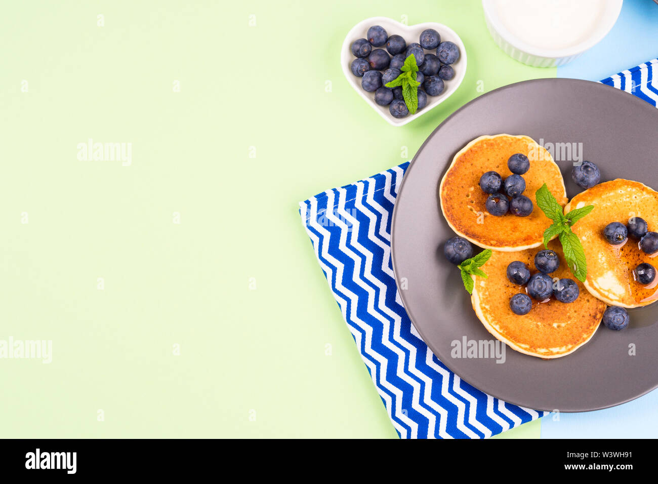 Pancakes served with fresh blueberries on gray plate over geometrical background. Healthy home made breakfast concept - Stock Image