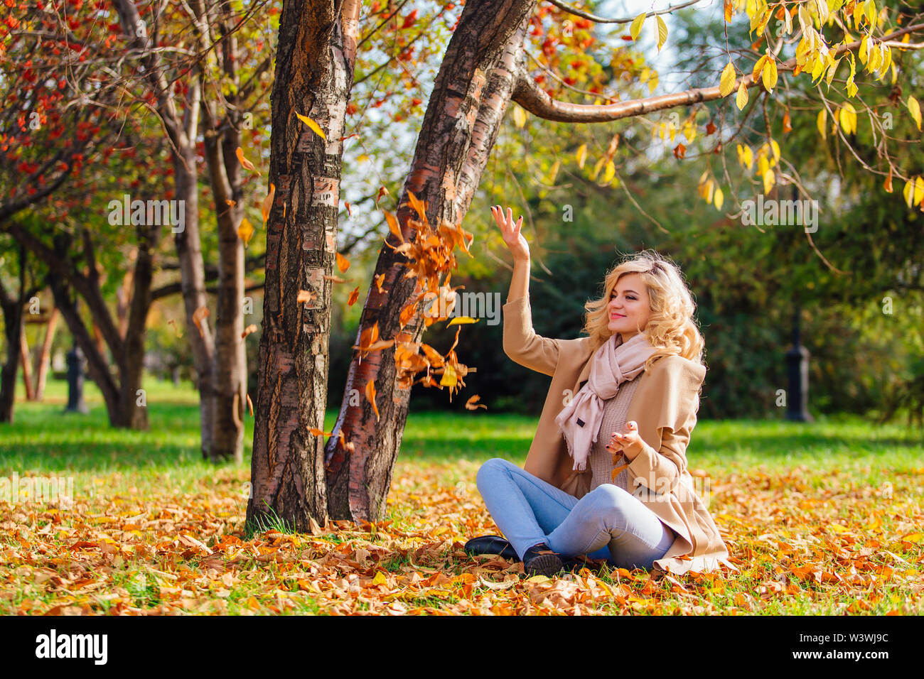 Young beautiful blonde woman throwing up fallen autumn leaves over her head sitting on the ground - Stock Image