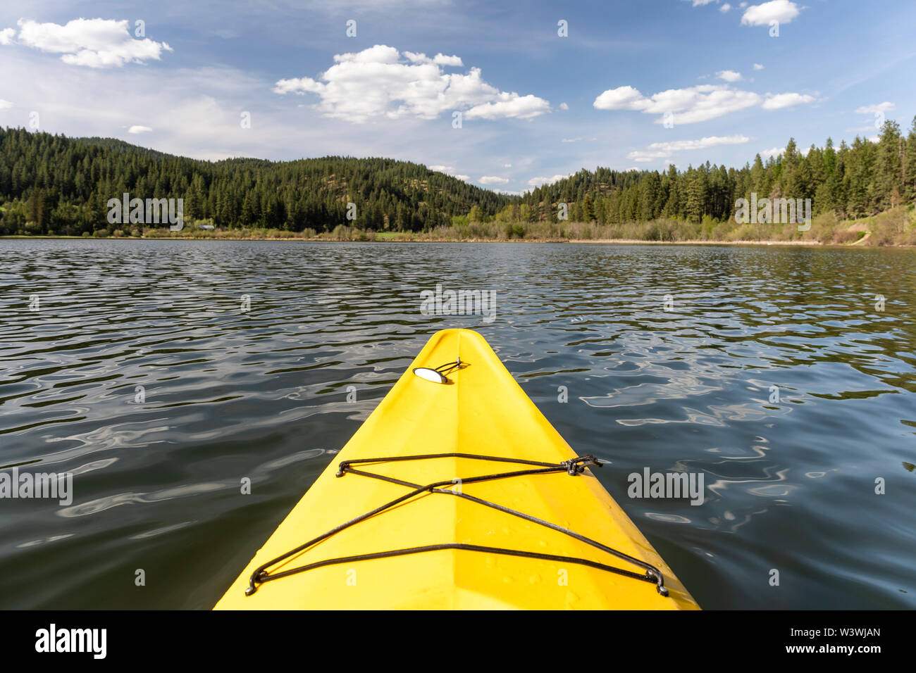 Kayaking in a yellow boat on Couer D'Alene Lake on a sunny spring day - Stock Image
