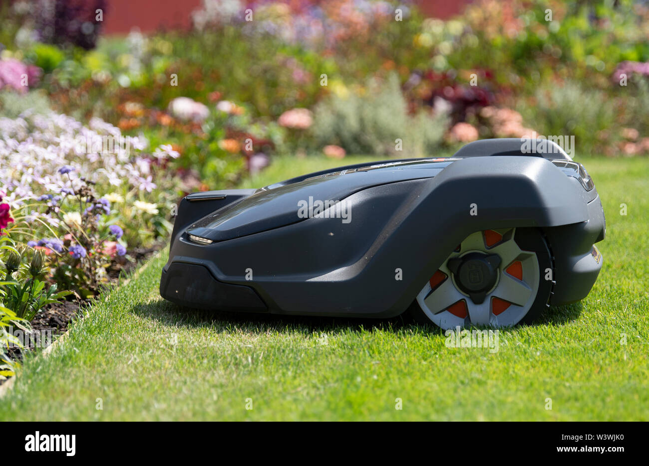 Wittstock, Germany. 17th July, 2019. A Husqvarna mowing robot drives across a meadow at the National Garden Show and turns around in front of the lawn edge. Credit: Soeren Stache/dpa/Alamy Live News - Stock Image