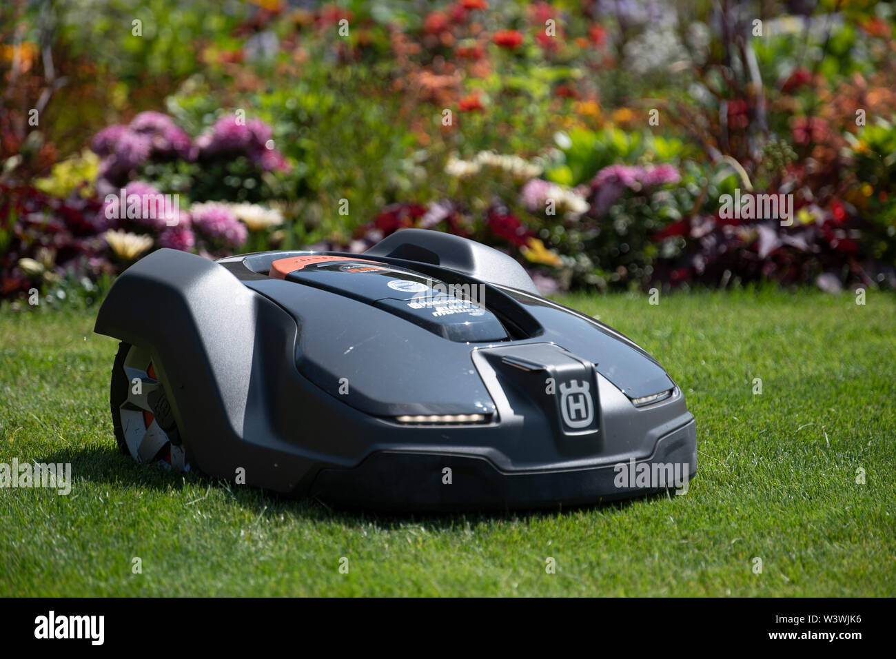 Wittstock, Germany. 17th July, 2019. A Husqvarna mowing robot drives across a meadow at the State Garden Show. Credit: Soeren Stache/dpa/Alamy Live News - Stock Image