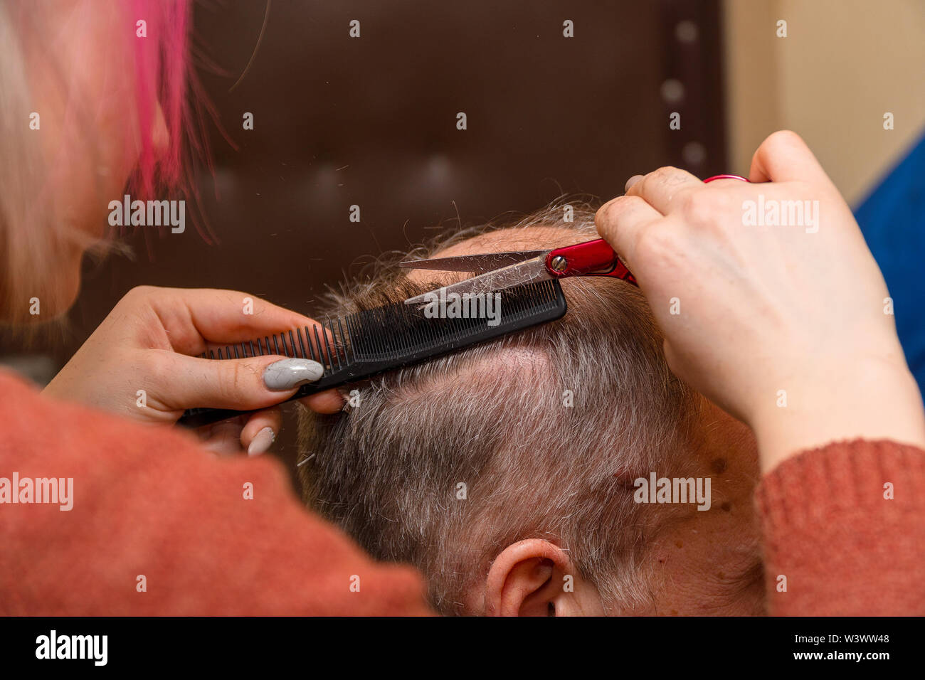 Woman hairdresser cuts a man with a receding hairline with scissors. Selective focus - Stock Image