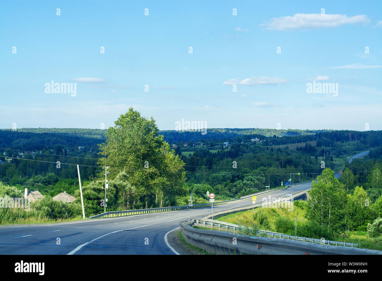Asphalt road going through the forest on a summer sunny day. Around the green trees and Christmas trees. Clear blue sky. Journey by Siberia - Stock Image