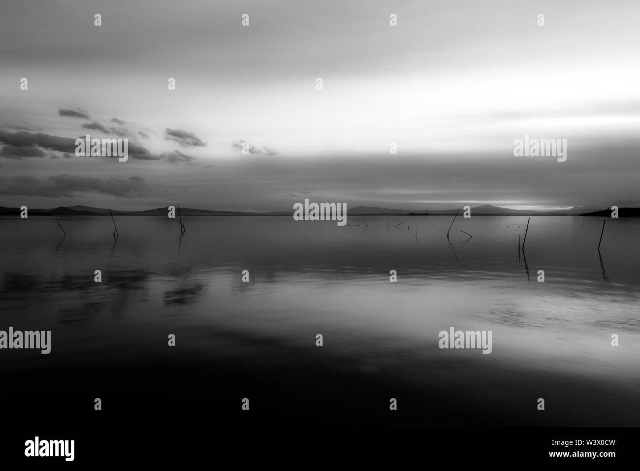 Beautiful and symmetric sunset over Trasimeno lake (Umbria, Italy) - Stock Image