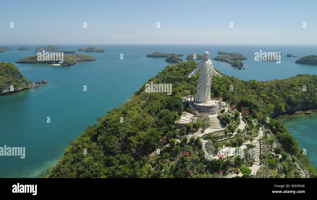 Statue of Jesus Christ on Pilgrimage island in Hundred Islands National Park, Pangasinan, Philippines. Aerial view of group of small islands with beaches and lagoons, famous tourist attraction, Alaminos. - Stock Image