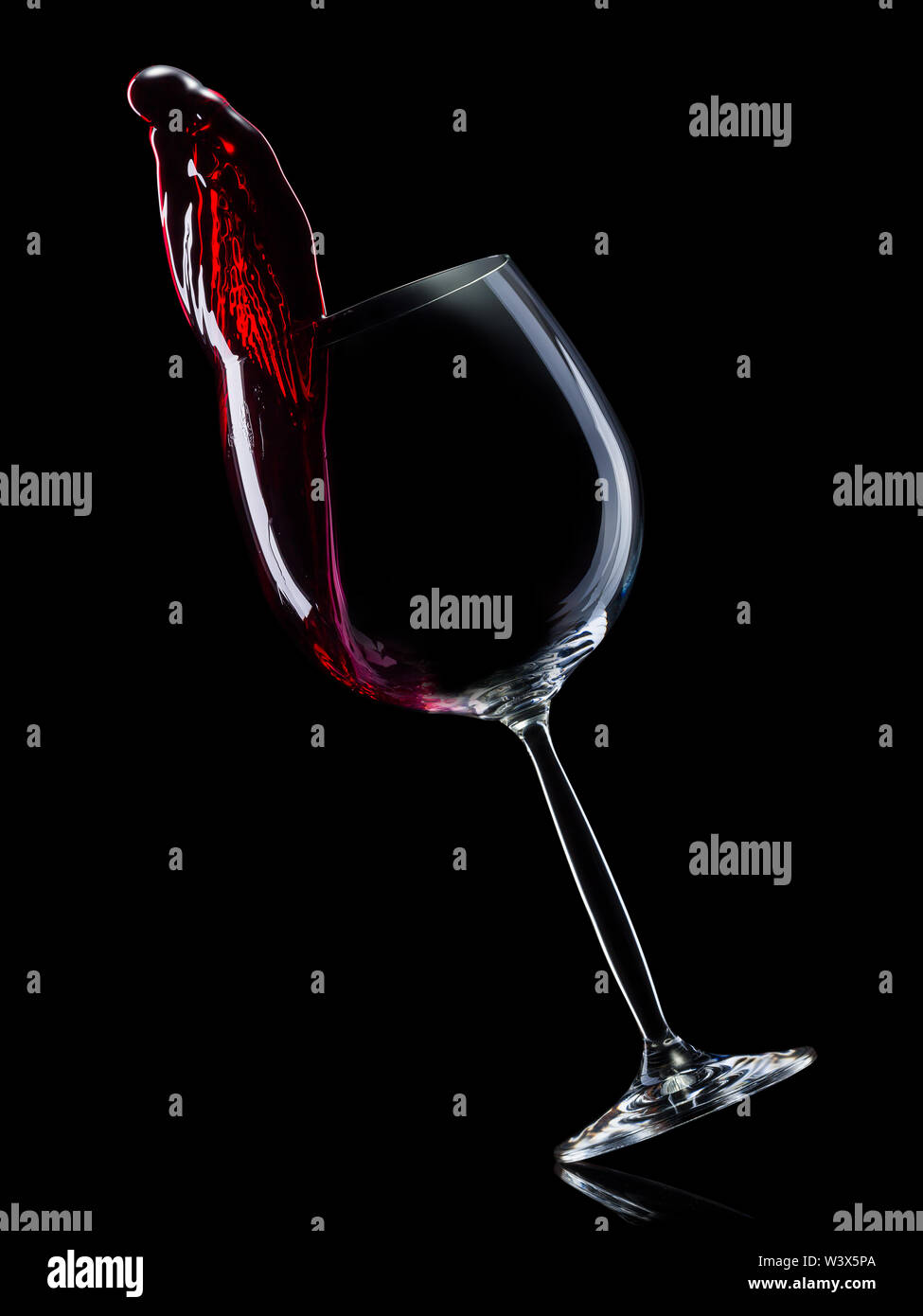 Glass for red wine with splashes isolated on black background. - Stock Image