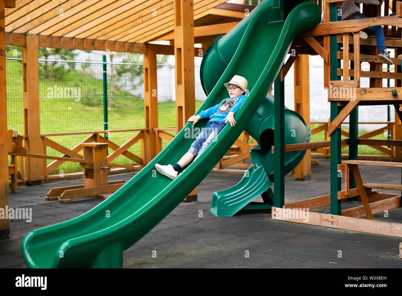 Child with straw hat and big glasses playing on outdoor playground. Active kid on colorful swing. Healthy summer activity for children. Little boy swi - Stock Image