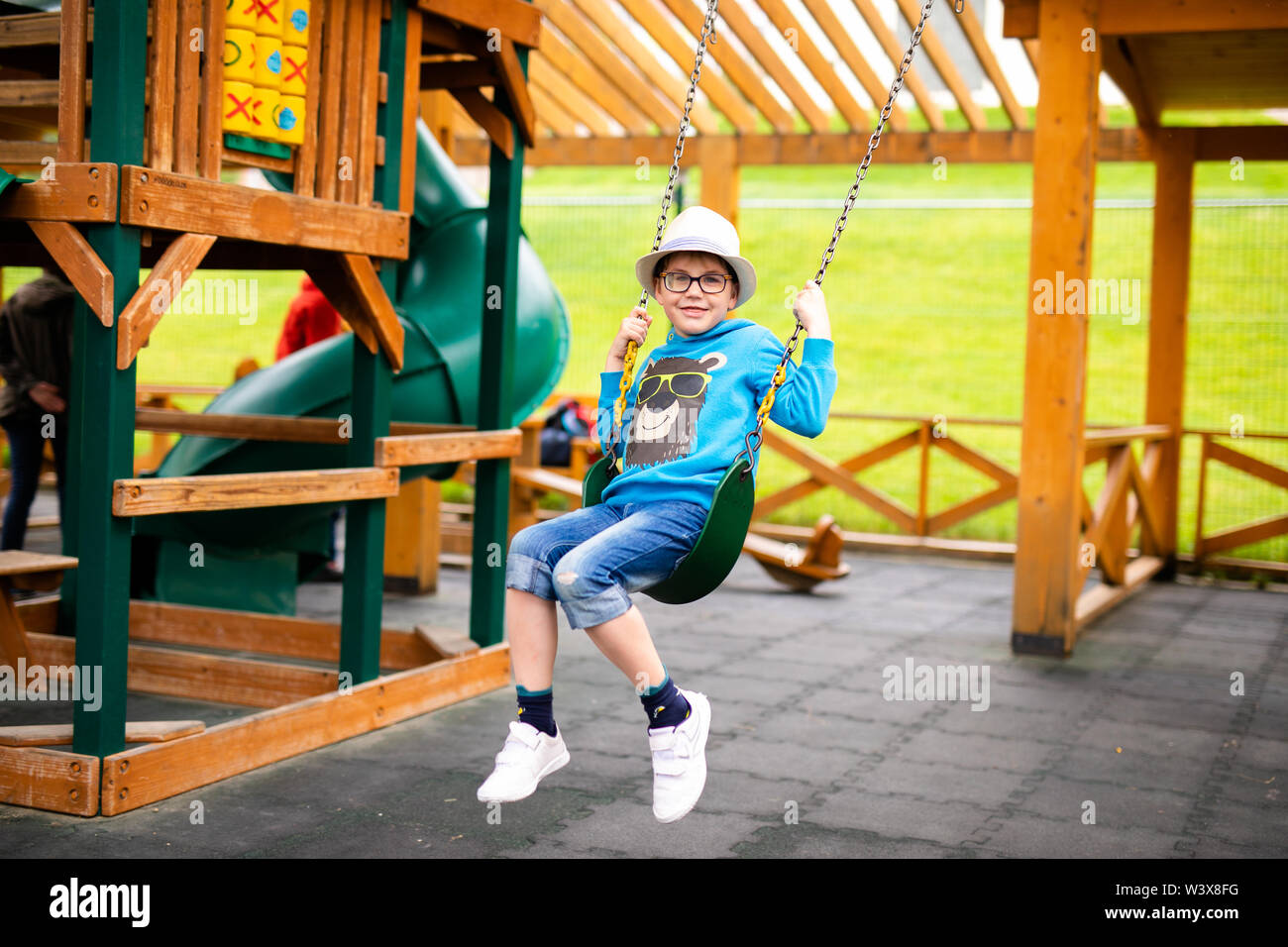 Child with straw hat and big glasses playing on outdoor playground. Active kid on colorful swing. Healthy summer activity for children. Little boy swi Stock Photo