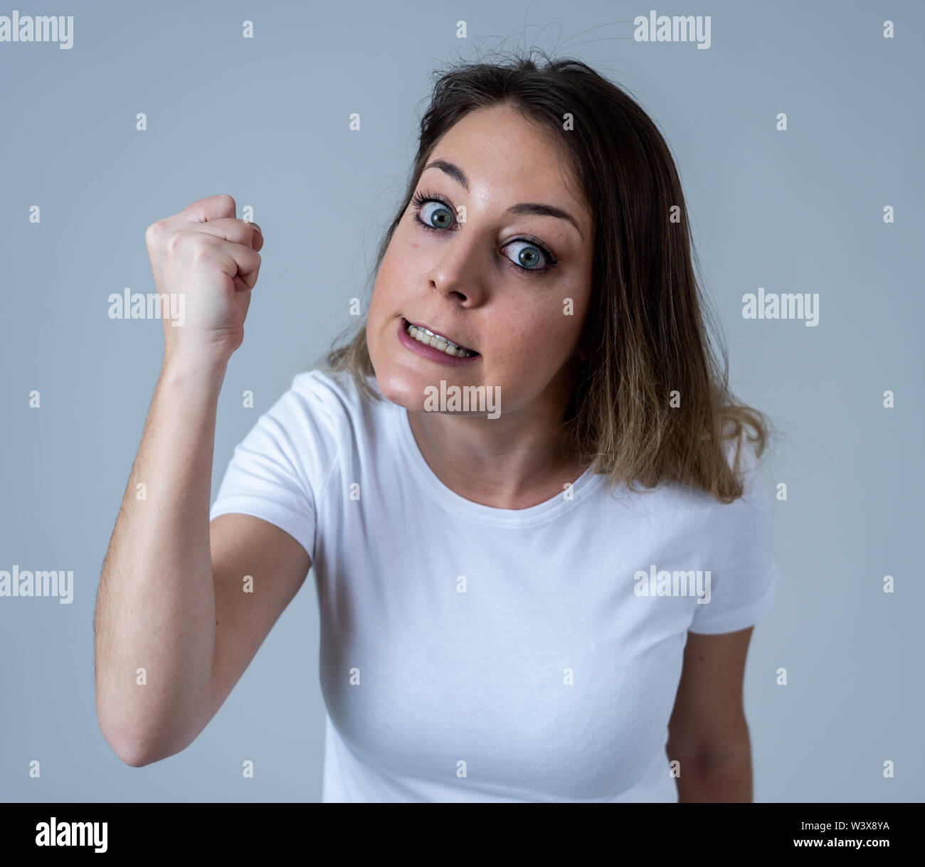 Close up portrait of young attractive caucasian woman with an angry face. Looking mad and crazy shouting and making furious gestures. Isolated on neut - Stock Image
