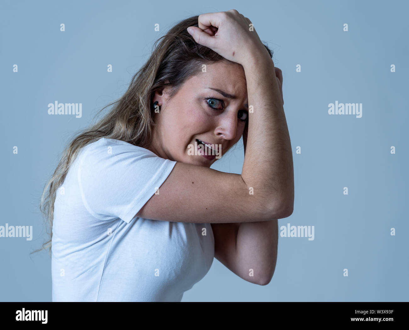Close up of young woman feeling scared and shocked making fear, anxiety gestures. Looking terrified and desperate. People and Human expressions and em - Stock Image