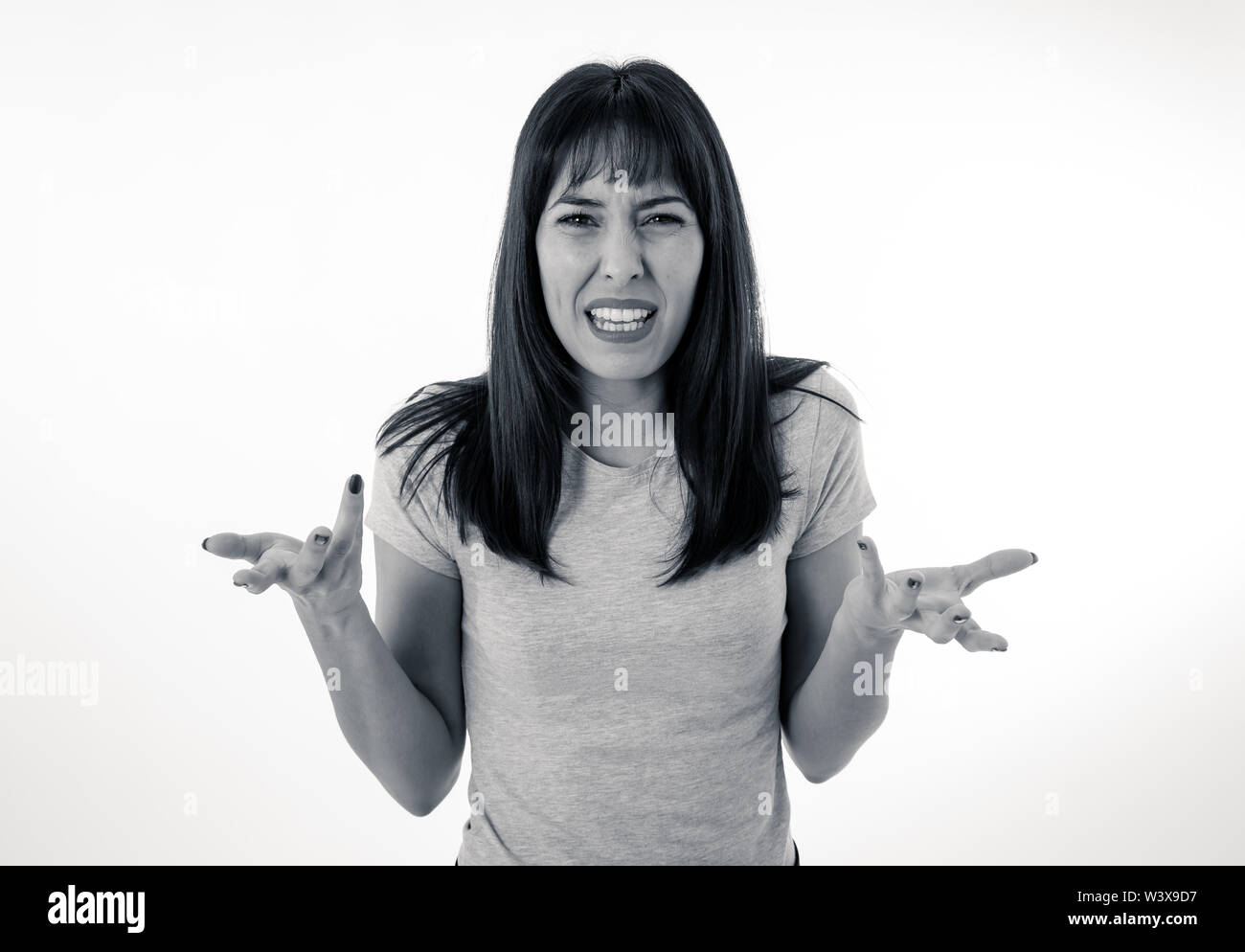 Close up portrait of young attractive caucasian woman with an angry face. Looking mad and crazy shouting and making furious gestures. Isolated on blac - Stock Image