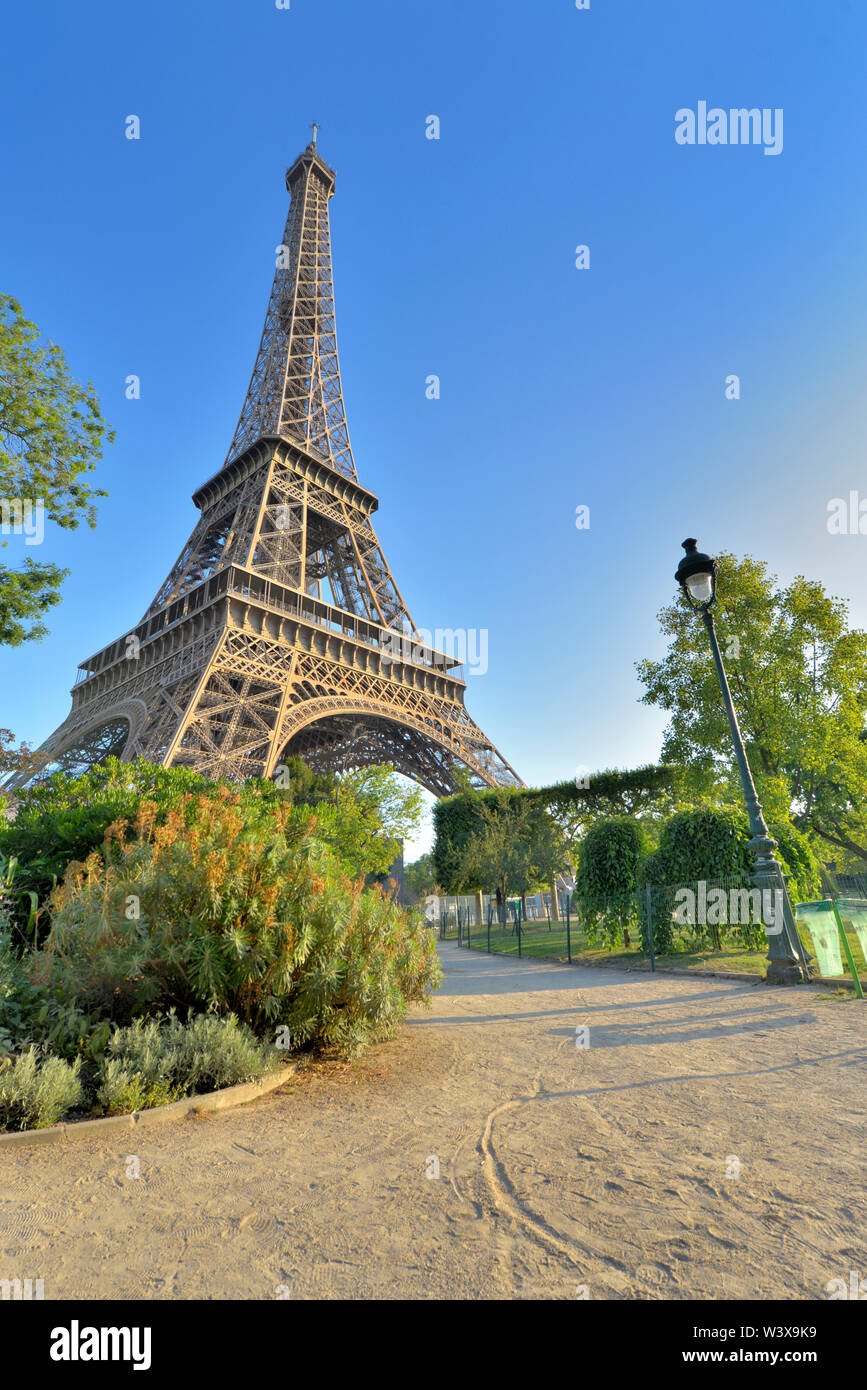 Eiffel tower in Paris view from a little path in garden of Champs de Mars - Stock Image