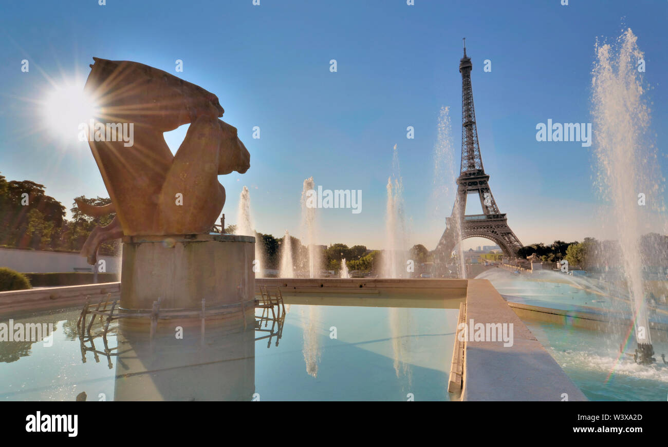 view on Eiffel tower from the ponds of Trocadero place and sun shinny behind sculpture Stock Photo