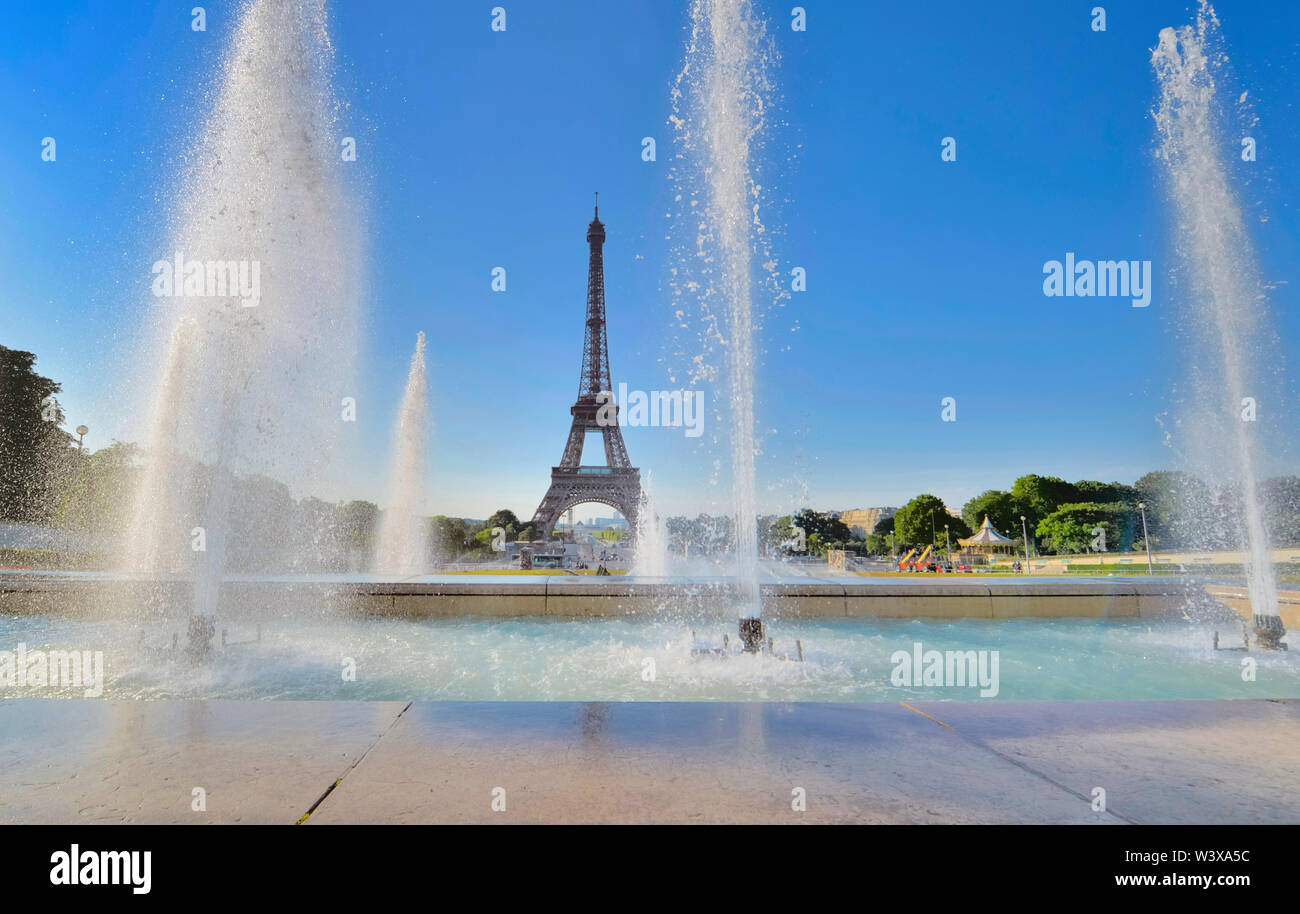 water jets in trocadero fountain on blue sky with  silhouette of eiffel tower - Stock Image