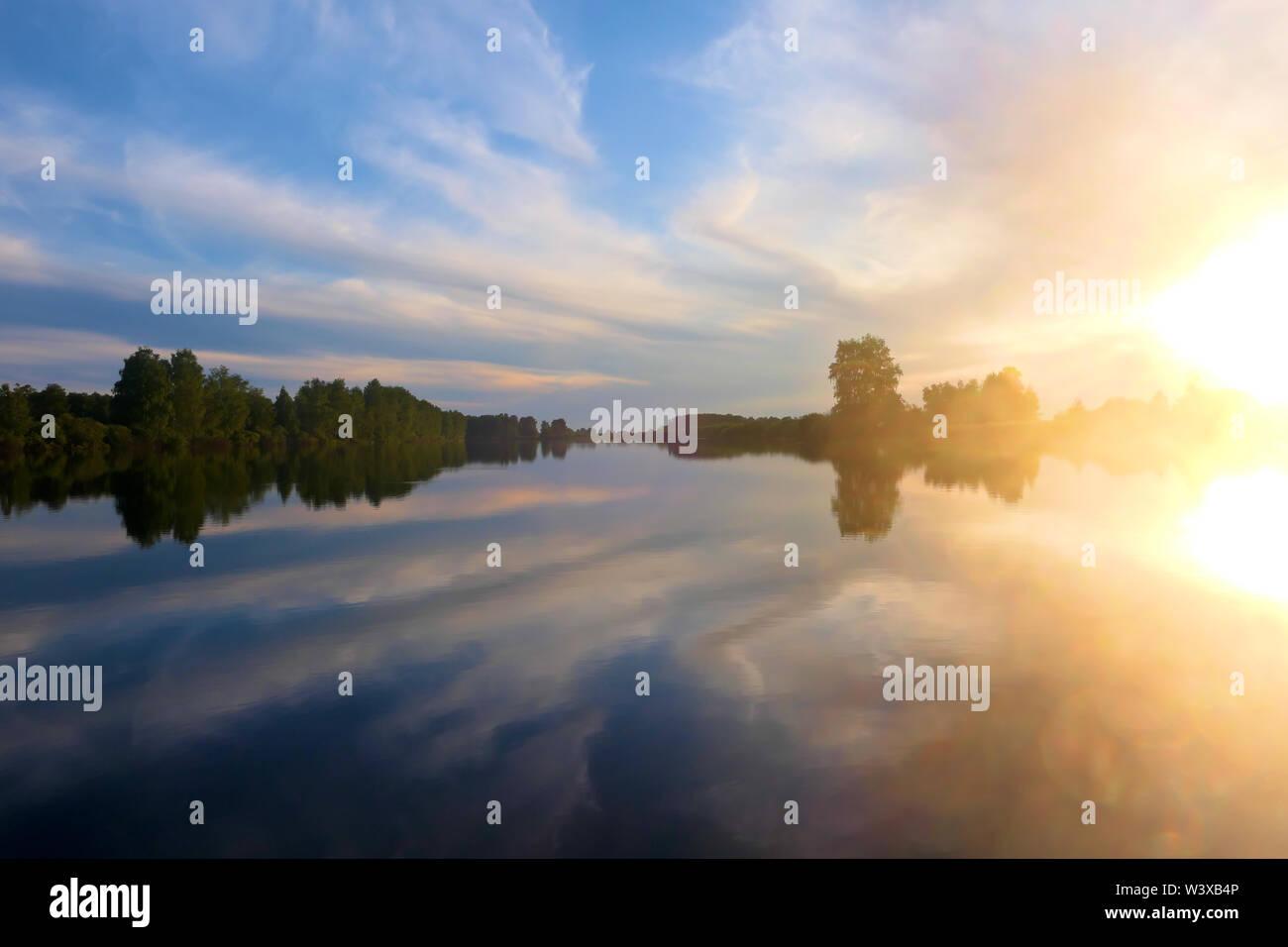 Bright beautiful sunset over lake - Stock Image