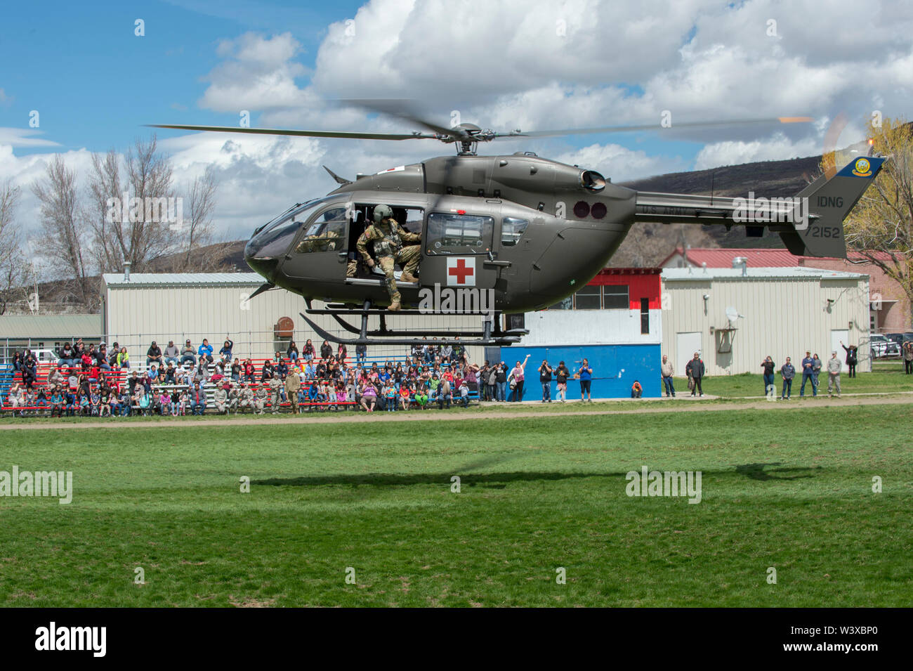 Students from the Owyhee Combined School on the Duck Valley Indian Reservation watch a UH-72 Lakota Helicopter take off from a field, flown by members of the Idaho National Guard, 24 April, 2019, Owyhee, Nevada. Members of the Idaho National Guard traveled to the Duck Valley Indian Reservation to conduct a health fair with the community. - Stock Image