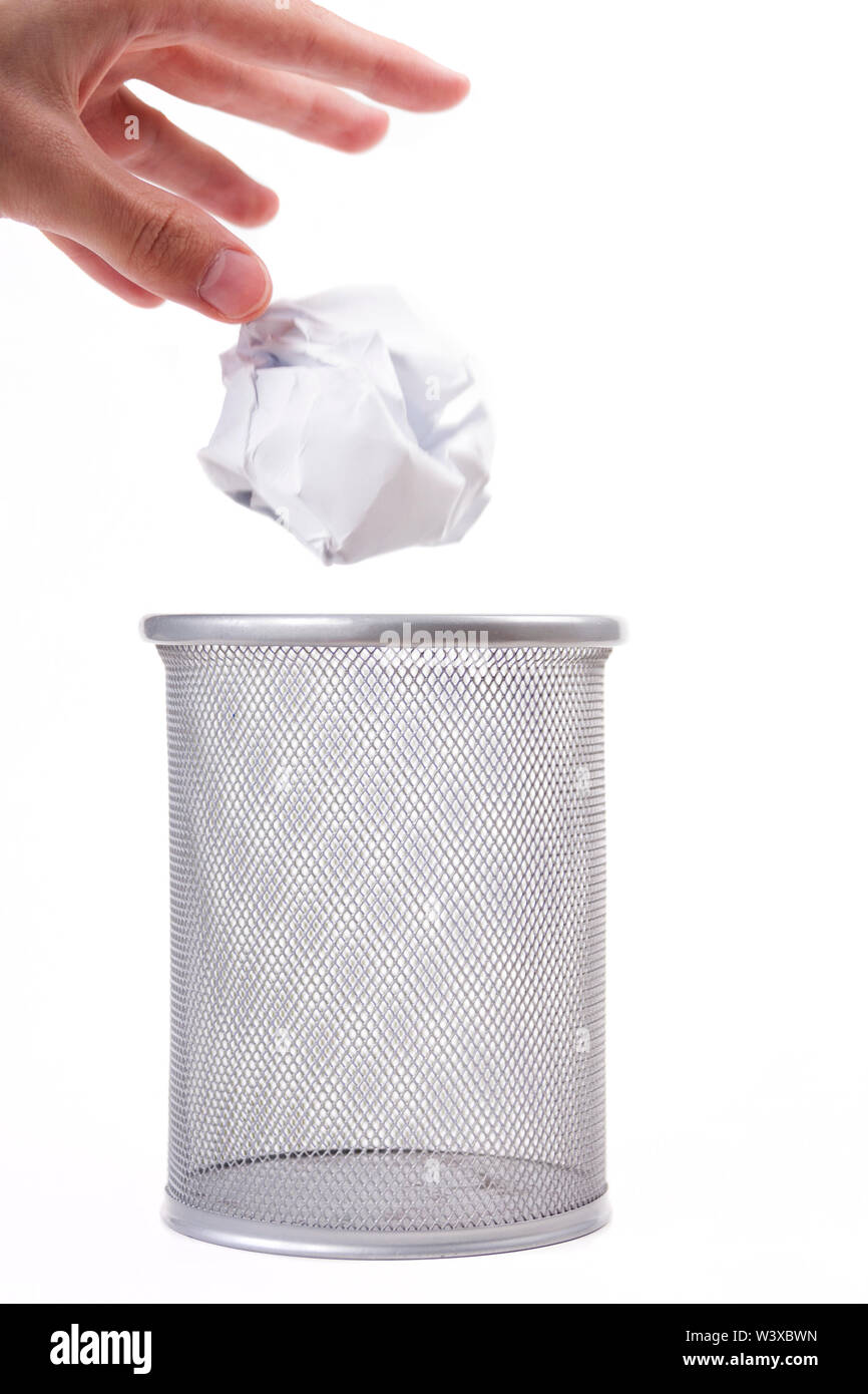 A human hand gently dropping crumpled paper ball into an empty metal trash can. Throwing away garbage, trashing an unused idea concept, gentle gesture - Stock Image