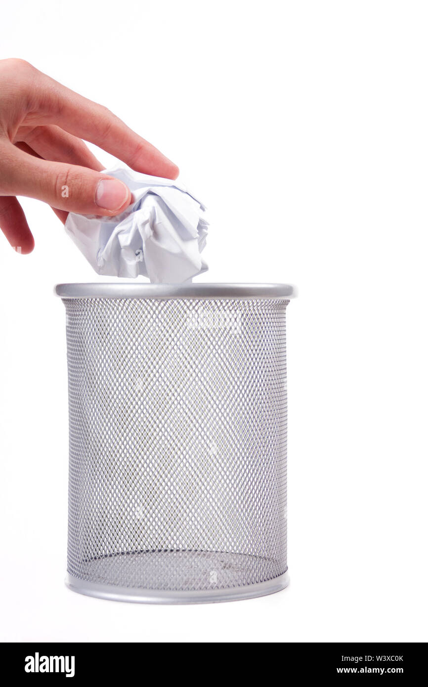 A human hand gently putting a crumpled paper ball in a empty metal trash can. Throwing away garbage, trashing an unused idea concept, gentle gesture - Stock Image