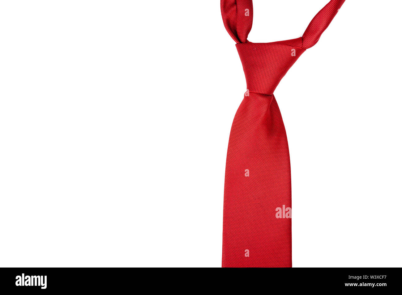 A classic red tie isolated on white background. Formal men clothes, suit elements and general red color concept, nobody - Stock Image