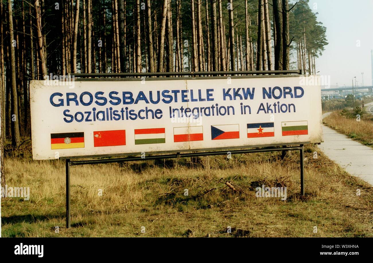 FILED - 01 January 1990, Berlin, Lubmin: Mecklenburg-Western Pomerania/GDR/1990 Lubmin nuclear power plant near Greifswald. Block 5 is still under construction. A little later, the power plant is shut down for safety reasons. Later, an interim storage facility for radioactive waste will be set up there. The technology of the NPP was Soviet. The sign at the entrance shows the economic structure of the East Block. GDR, Soviet Union, Bulgaria, Poland, Czechoslovakia and Hungary work together. A total of 5 blocks were planned, 4 were in operation, each with a capacity of 400 MW. All decommissi - Stock Image