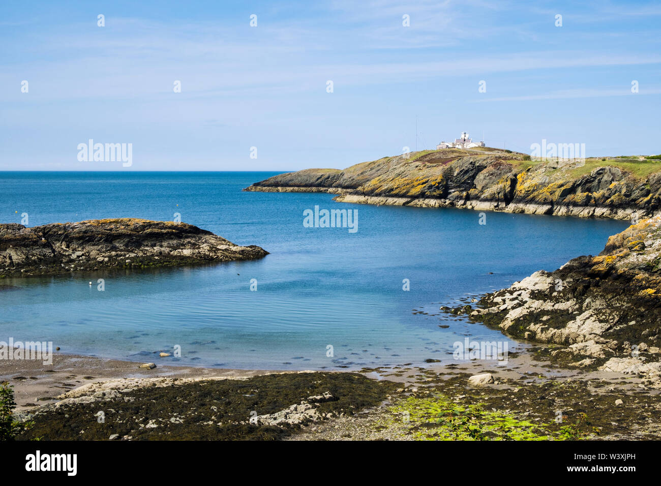 Calm blue sea in Porth Eilian and Point Lynas / Trwyn Eilian lighthouse. Llaneilian, Isle of Anglesey, north Wales, UK, Britain - Stock Image