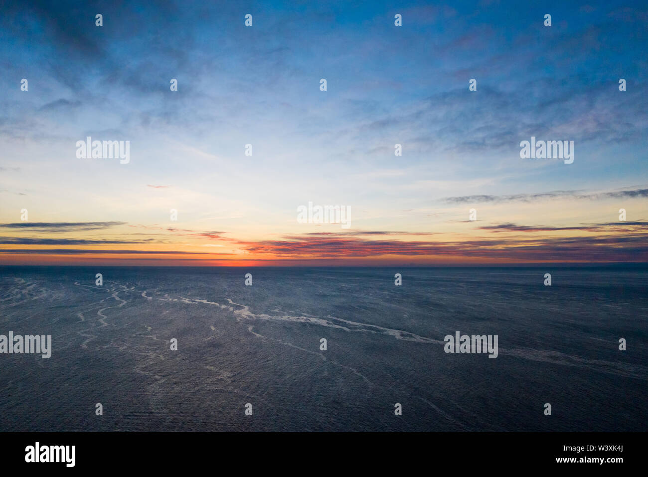 Sunset over the sea in calm weather. Calm sea in the evening. The sun on the horizon. - Stock Image