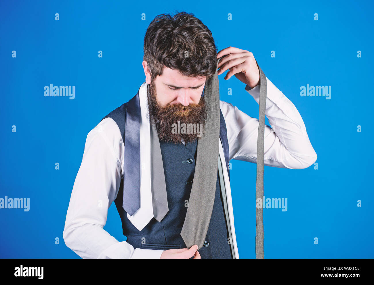 Hard choice to make. Bearded man choosing tie from luxury collection, choice concept. Salesman offering a good choice of design neckties. Brutal hipster making a choice. - Stock Image