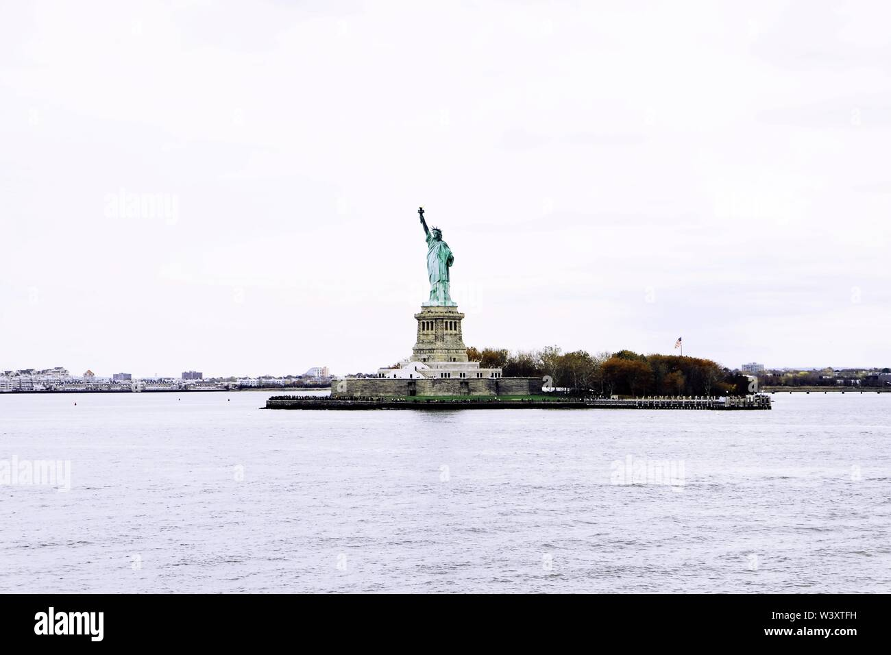 A distant wide shot of The Statue of Liberty with a clear white sky in the background - Stock Image