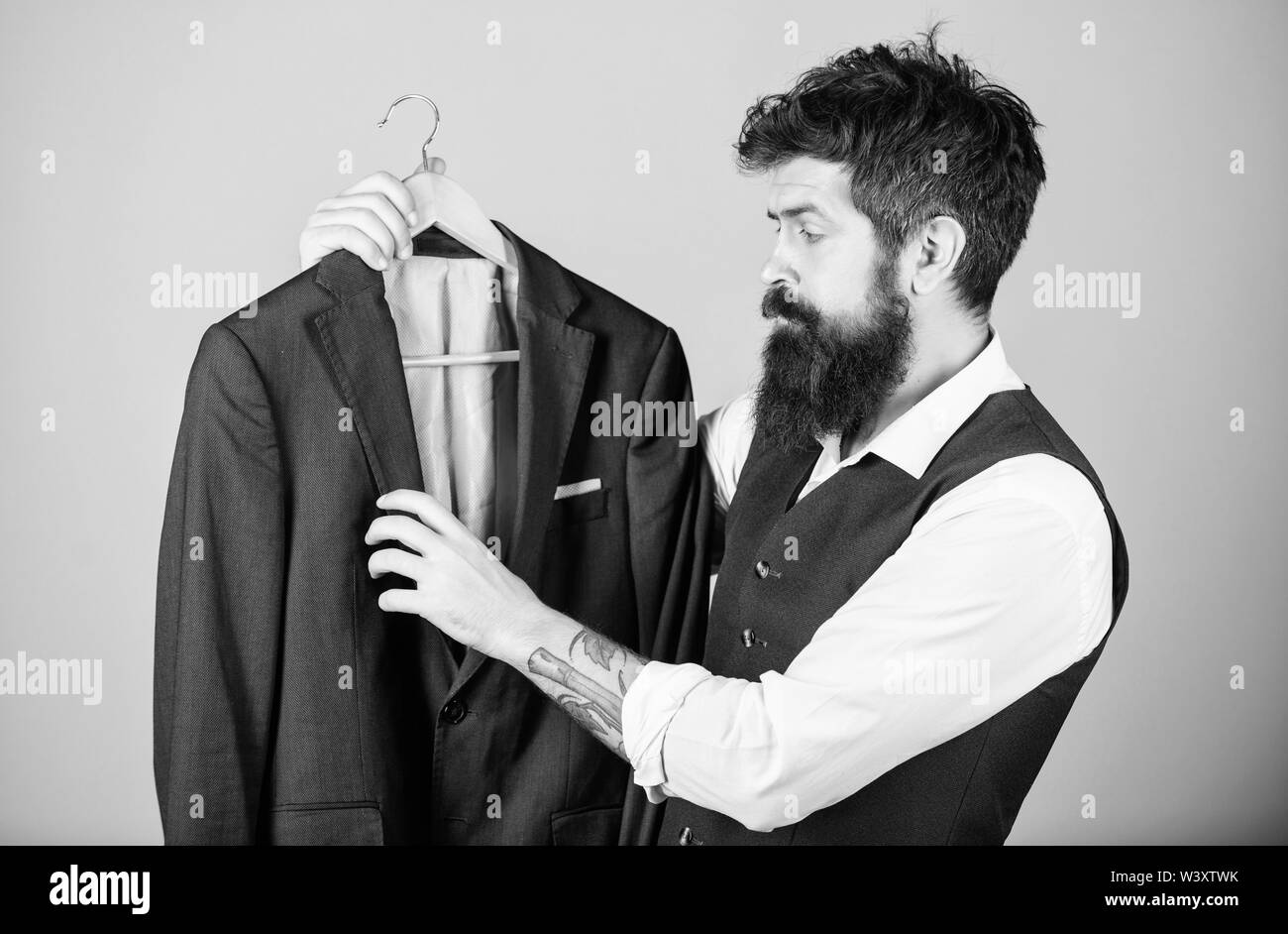 Tailoring and clothes design. Perfect fit. Custom made to measure. Tailored suit concept. Designing made to measure suit. Custom made suit. Man bearded fashion couturier tailor. Elegant custom outfit. - Stock Image