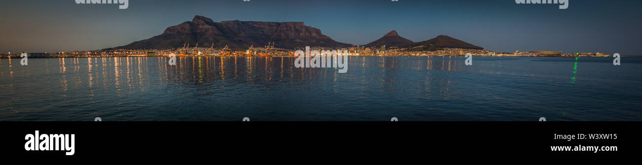 The city lights of Cape Town reflect in the waters of Table Bay in a panoramic photo taken from a ship in the Atlantic Ocean. - Stock Image
