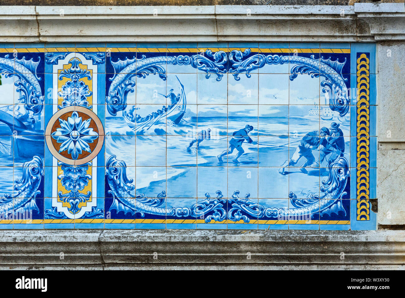 Traditional azulejo panels in blue and white represent fishing boat on the facade of an old villa of a wealthy industrialist. - Stock Image
