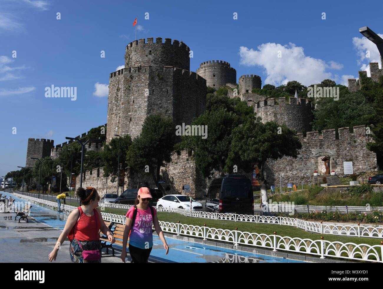 Istanbul, Turkey. 18th July, 2019. Two tourists walk in front of the Rumeli Fortress in Istanbul, Turkey, July 18, 2019. Turkey's biggest city Istanbul allured a record number of tourists during the first five months of this year, thanks to an environment of peace, affordable prices and diversified tourism products. Between January and May, 5.4 million foreigners visited Istanbul, marking a year-on-year increase of 11 percent, according to the data unveiled by the Istanbul Provincial Directorate of Culture and Tourism. Credit: Xu Suhui/Xinhua/Alamy Live News - Stock Image