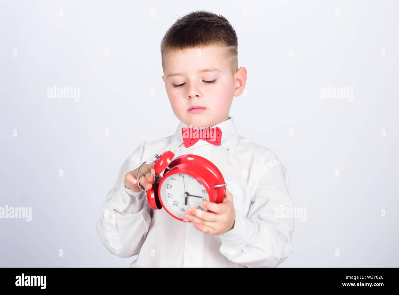 happy child with retro clock in bow tie. tuxedo kid. Happy childhood. little boy with alarm clock. Time to relax. Party time. Businessman. Formal wear. Time management. Morning. tuxedo time. - Stock Image