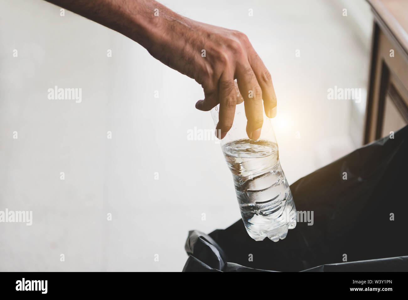 Closeup of hand throwing garbage into black bag bin. Ecology and environment. Pollution and recycled concept. - Stock Image