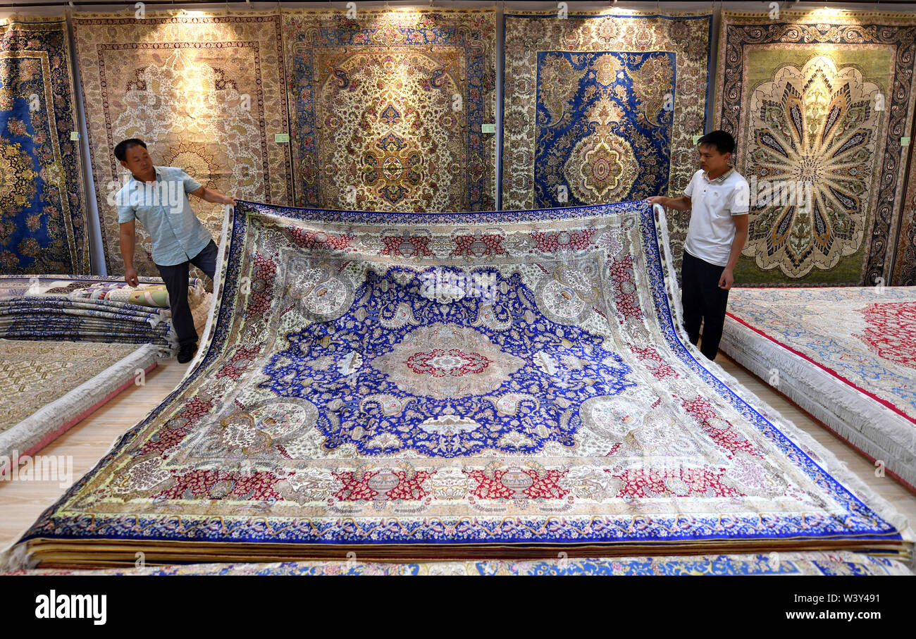 Nanyang, China's Henan Province. 17th July, 2019. Workers of Nanyang Yuxiang Craftworks Co., Ltd. unfold a silk carpet in Nanyang, central China's Henan Province, July 17, 2019. The silk carpets made in Nanzhao County, featuring the Persian style, have been exported to more than 30 countries and regions, boosting the local economy and farmers' income. Credit: Li Jianan/Xinhua/Alamy Live News - Stock Image