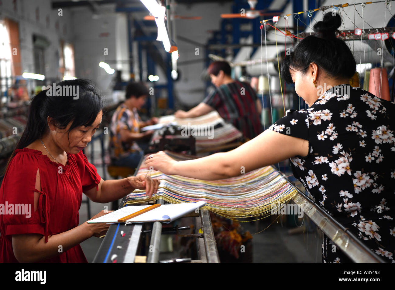 Nanyang, China's Henan Province. 17th July, 2019. Workers weave silk carpets at the workshop of Nanyang Yuxiang Craftworks Co., Ltd. in Nanyang, central China's Henan Province, July 17, 2019. The silk carpets made in Nanzhao County, featuring the Persian style, have been exported to more than 30 countries and regions, boosting the local economy and farmers' income. Credit: Li Jianan/Xinhua/Alamy Live News - Stock Image