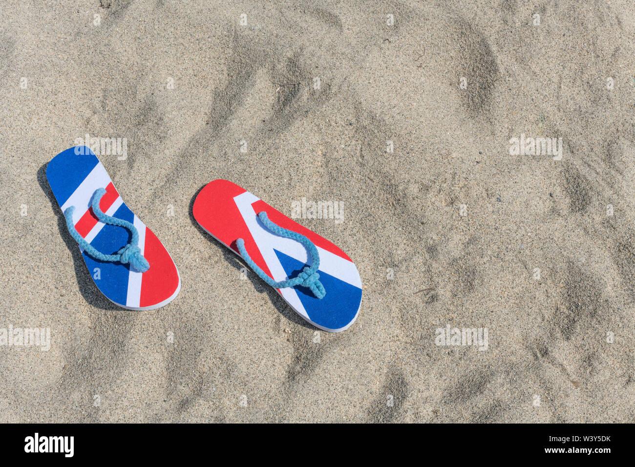 GB flag / Union Jack flip flops on sandy beach - metaphor UK staycation, holidays at home, staycation Cornwall, seaside holiday, flip-flop footwear. - Stock Image