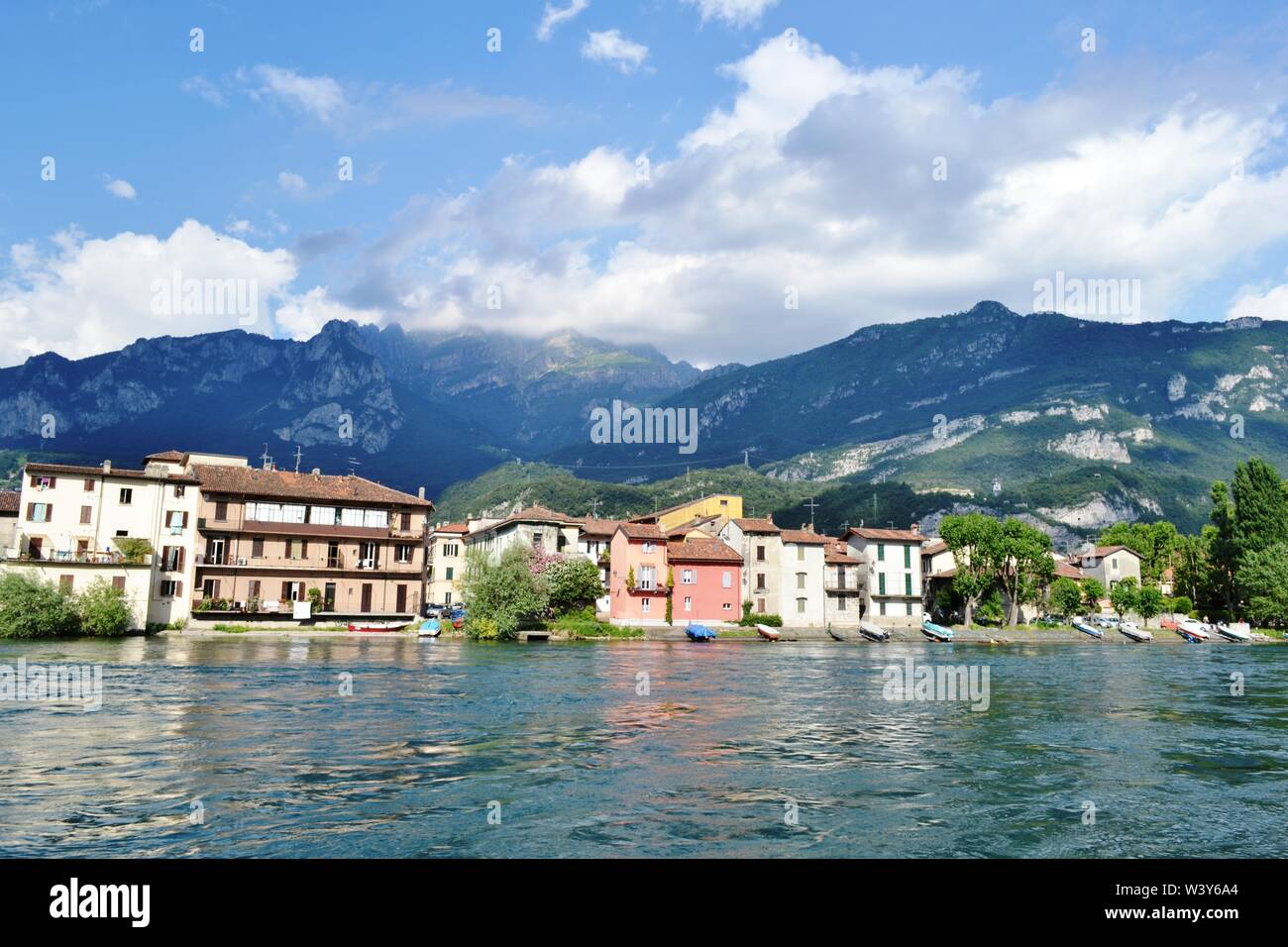 Panoramic view to Lecco Pescarenico fisherman district and the Adda river flowing in a sunny summer day with the Resegone mountain above them. Stock Photo