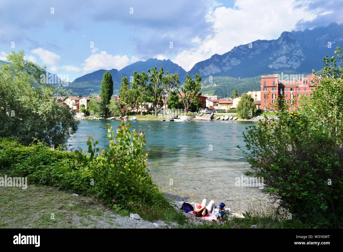 Lecco/Italy - July 10, 2014: Couple of tourist relaxing on the riverbank of Adda looking at Lecco Pescarenico fisherman district with mountains above. Stock Photo