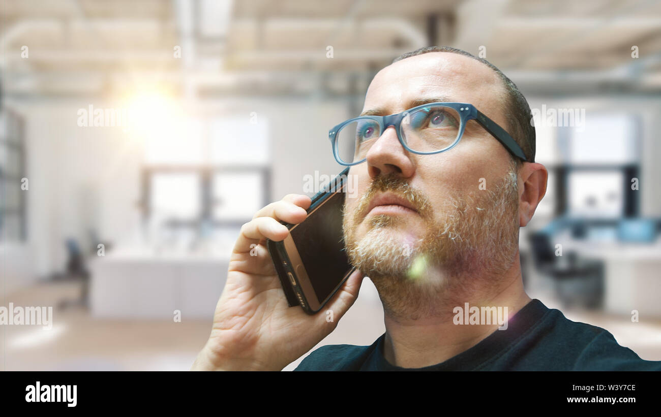 Young entrepreneur man using a mobile phone to get assistance. Office interior and empty copy space for Editor's text. - Stock Image