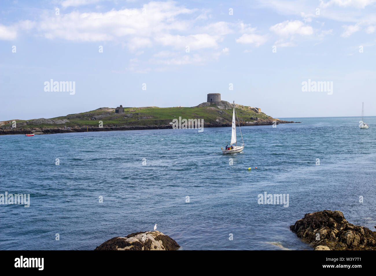 A yacht navigating the waters between Dalkey Island and Coliemore Harbour, Dalkey, Ireland.  There is an old Martello Tower on the island. - Stock Image