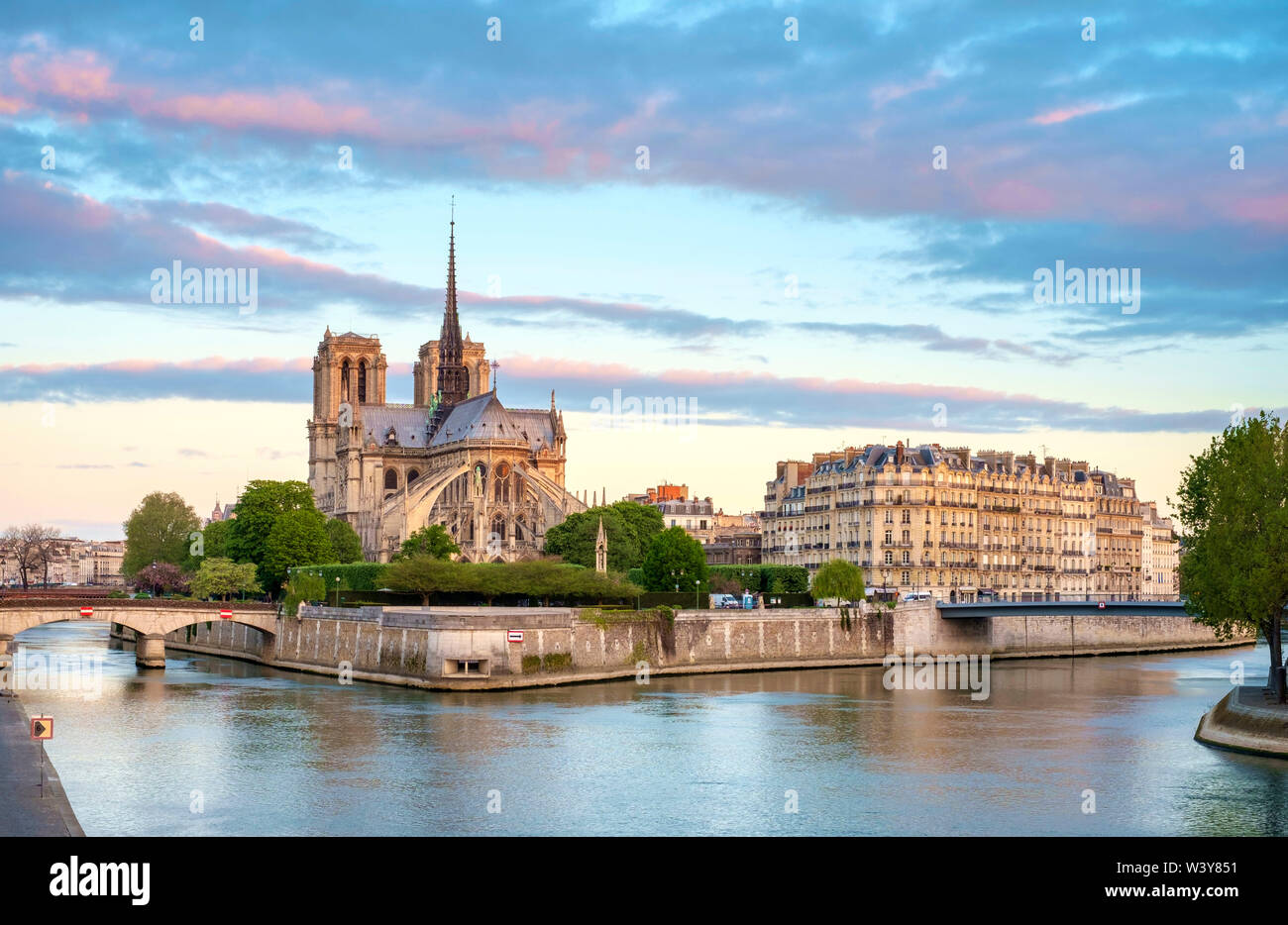 Notre Dame Cathedral on the banks of the Seine River at sunrise, Paris, Île-de-France, France - Stock Image