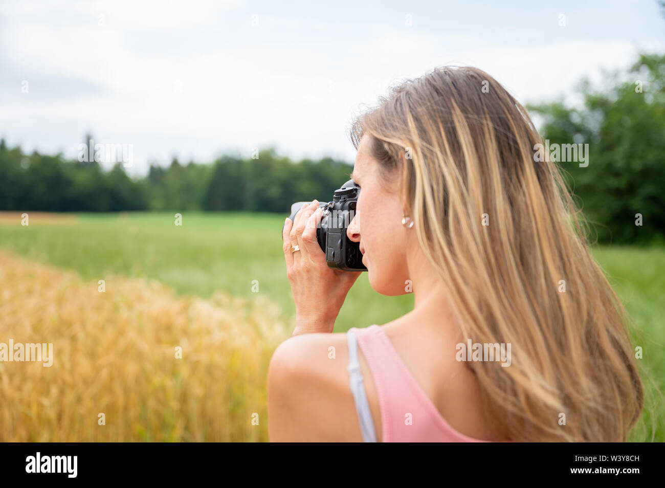 View from behind over the shoulder of a young female photographer taking a photo with black dslr camera of fields in nature. - Stock Image