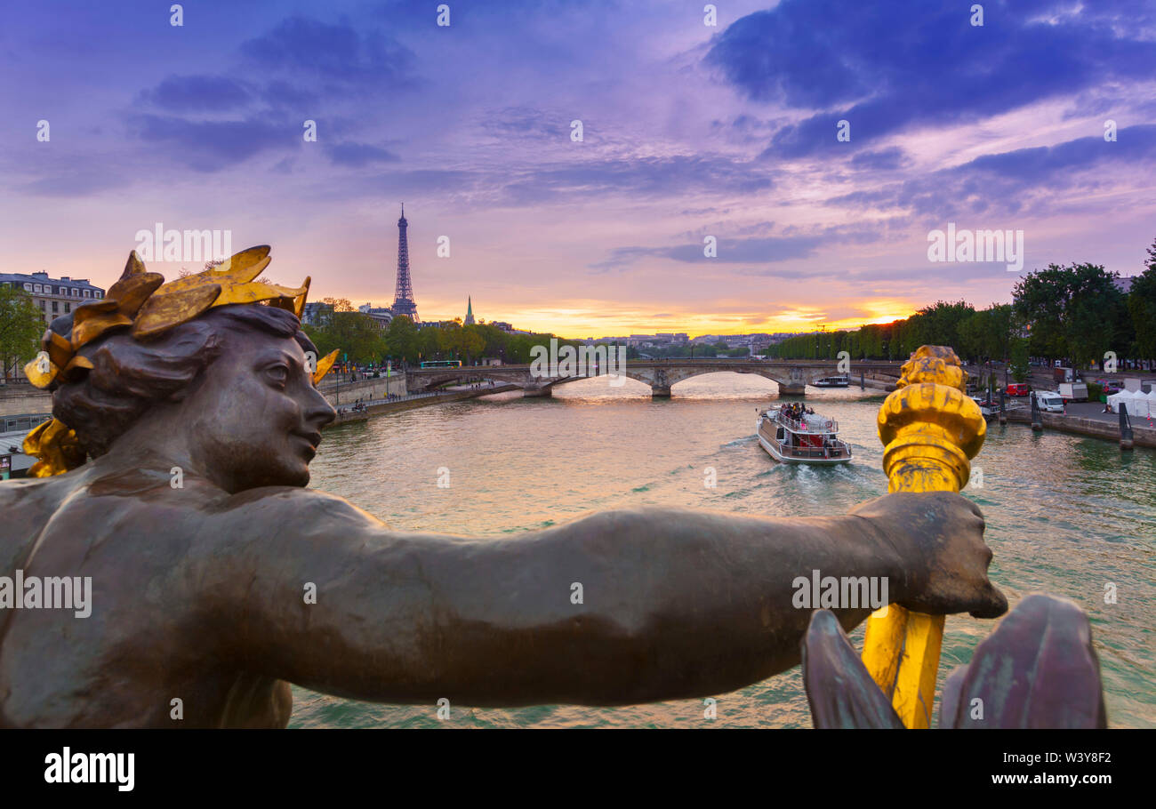 France, Paris, Pont Alexandre III with Eiffel Tower in background at dusk. Statue of the Nymphes de la Seine by Georges Recipon (1900) - Stock Image