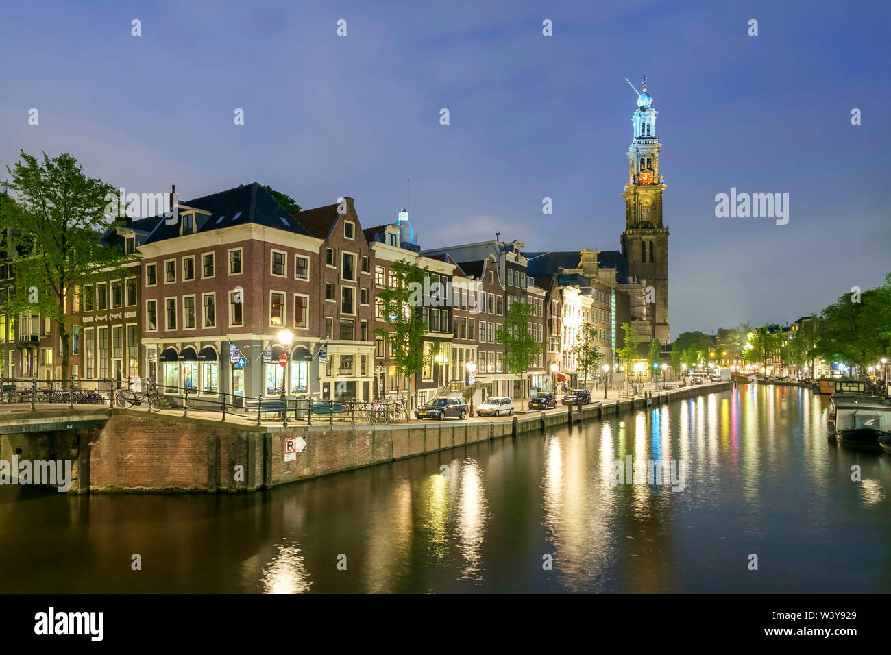 Intersection of Prinsengracht and Leidsegracht canals and tower of Westerkerk church at night, Amsterdam, North Holland, Netherlands - Stock Image